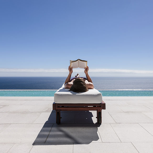 Lady reading book next to pool overlooking the beach.